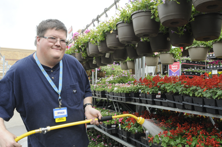Young man with disability at work in garden department of large retail store.
