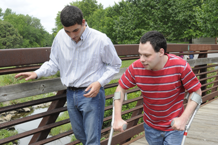 Young man walks through the park using crutches with an aide.
